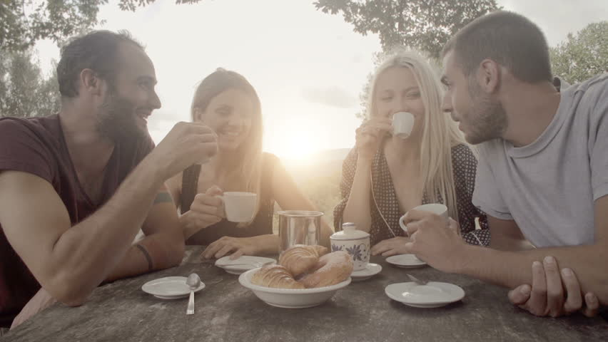 Group of four happy men and women friends smile, laugh and drink coffee during italian breakfast on a summer sunny day morning in tuscany, italy with visible sun - slow-motion dolly HD video footage | Shutterstock HD Video #8742349