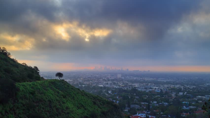 Sunrise with storm clouds rolling over city of Los Angeles cityscape. View from Hollywood Hills towards downtown LA. 4K UHD timelapse.