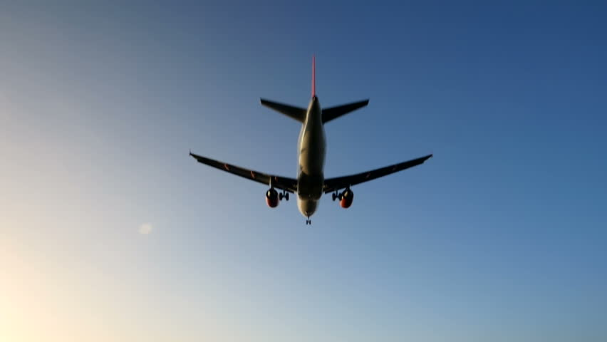 Airplane with red engines enters the frame overhead and flies away from the camera towards sunlight in a blue sky. Slow motion. | Shutterstock HD Video #8761300