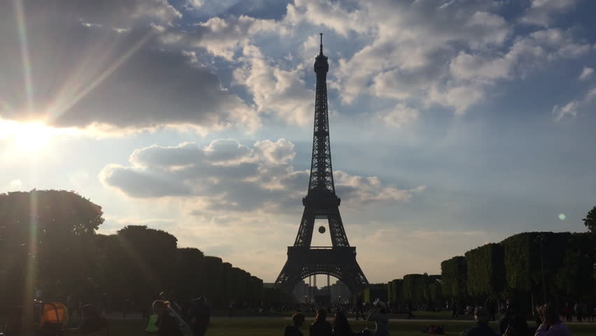Paris, France, June 2014. The Eiffel Tower at sunset from Champ de Mars, people enjoying the amazing sky that surrounds the landmark. | Shutterstock HD Video #8786635