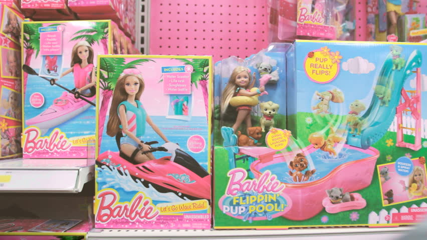 NEW YORK - FEB 10: Girl's hand taking Barbie Doll off store display shelf on February 10, 2015. Barbie is a fashion doll made by the American toy company Mattel, Inc. and launched in March 1959.