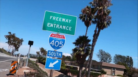 tilted pan of freeway entrance sign with palm trees