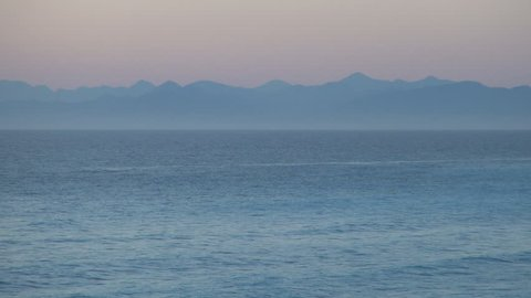 Dusk landscape with silhouette of mountains, orange sky and sea in a summer evening day.
