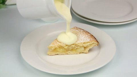 Slice of apple pie placed on a plate then cream poured over it.
