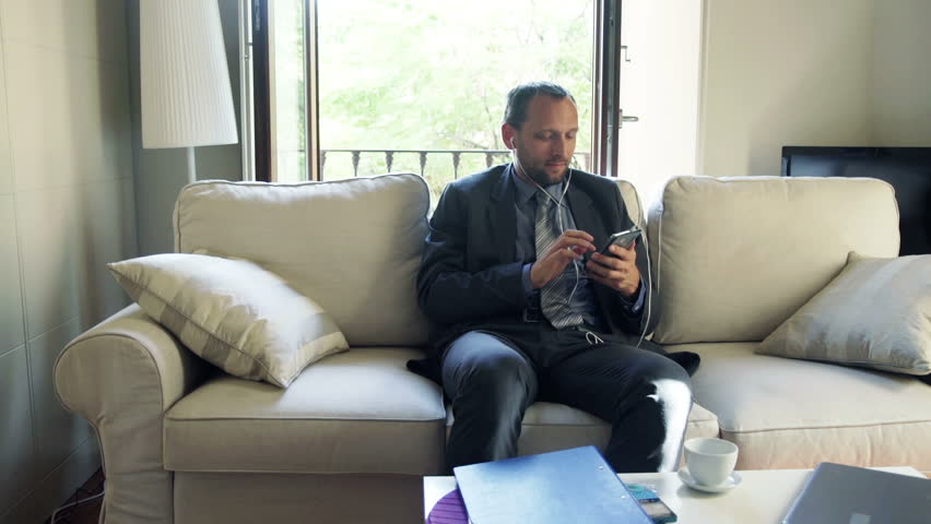 Businessman listening to music on cellphone and sitting on sofa at home