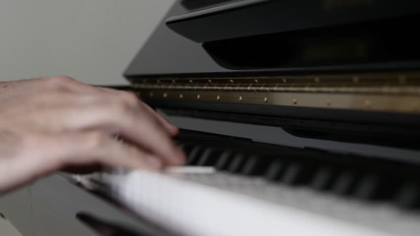 A beautiful shot of a man playing a song on a black and white piano