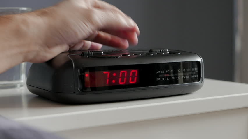 Alarm clock digital ringing, 7am, tired man pushes if of bed table