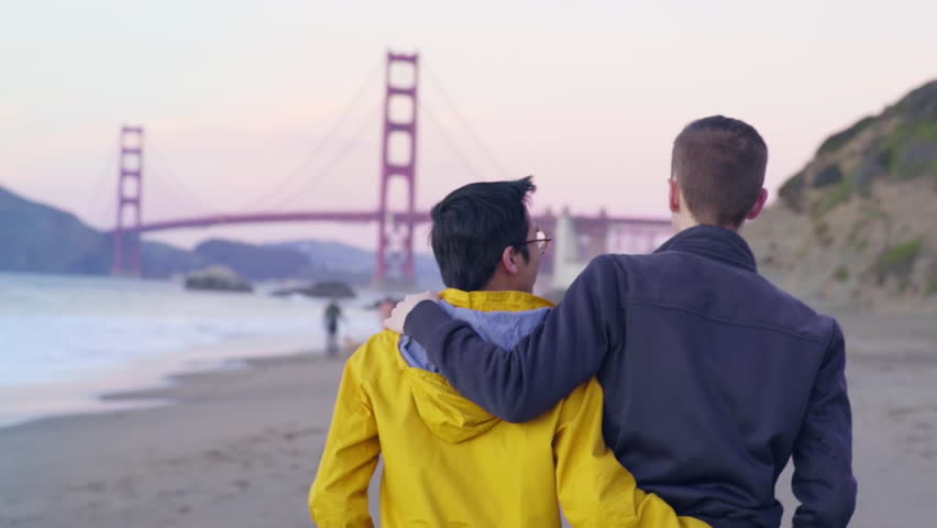 Gay Couple Walk On The Beach In San Francisco At Sunset (Golden Gate Bridge In Background)