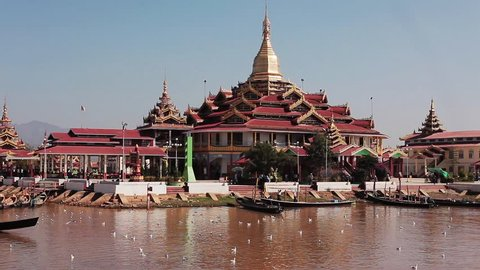 Inle lake temple with boats passing by