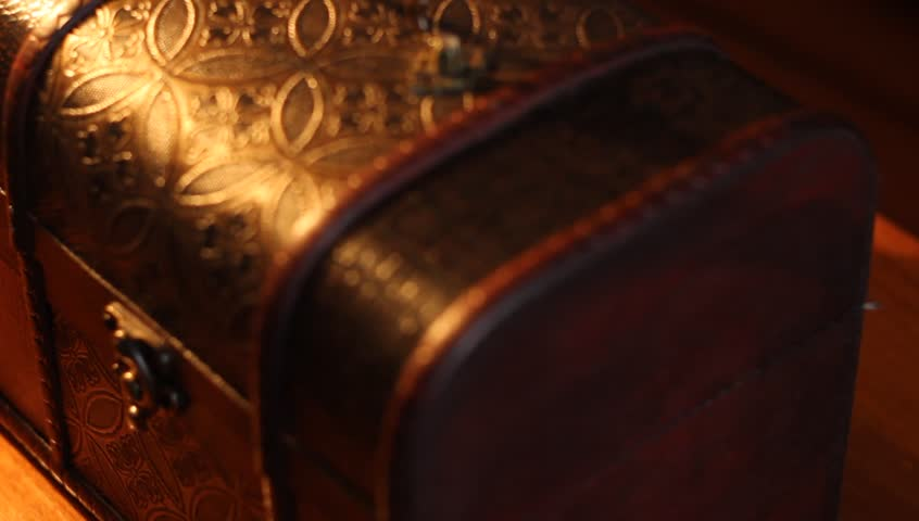 Hand pours coins into value wooden chest and plays greedy after with the money.   Shutterstock HD Video #8929285