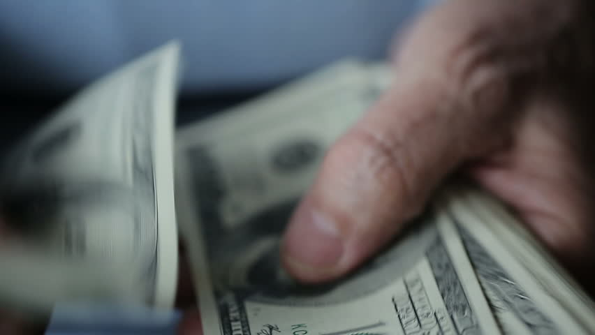 A businessman's hands counting hundred dollar bills at a table Royalty-Free Stock Footage #8930452