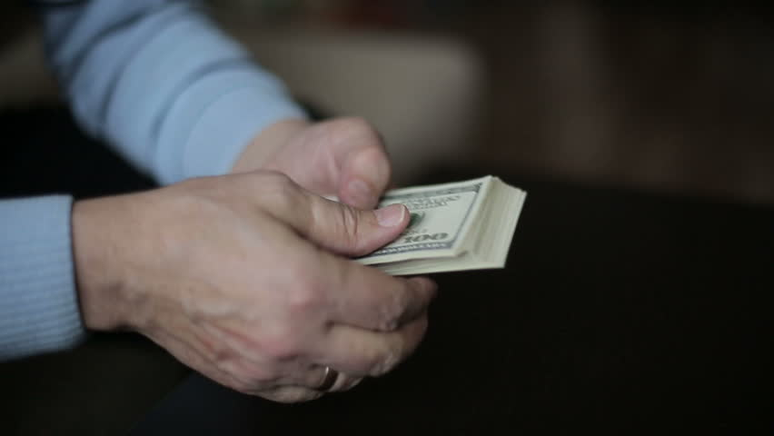 A businessman's hands counting hundred dollar bills at a table | Shutterstock HD Video #8930458