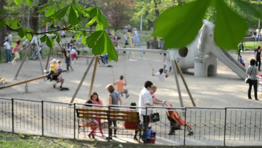 Kids and parents at playground enjoying a sunny afternoon in open air. Original ambience sounds included.