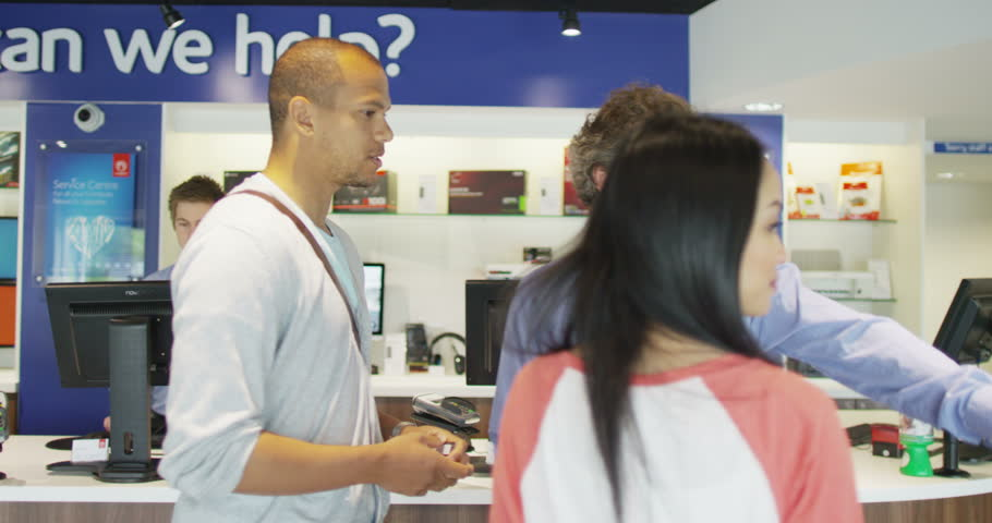 4K Helpful salesman serving customers in consumer electronics store showroom