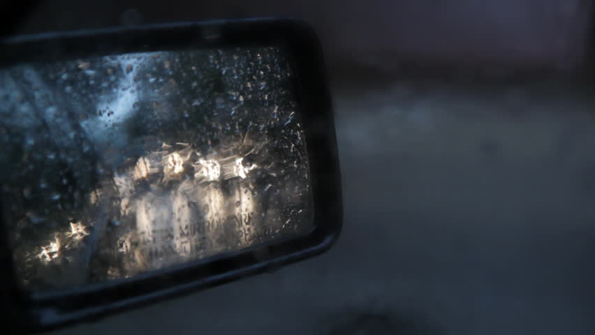 Side mirror with sound of rain. View of headlights in side mirror on rainy day. Good audio.