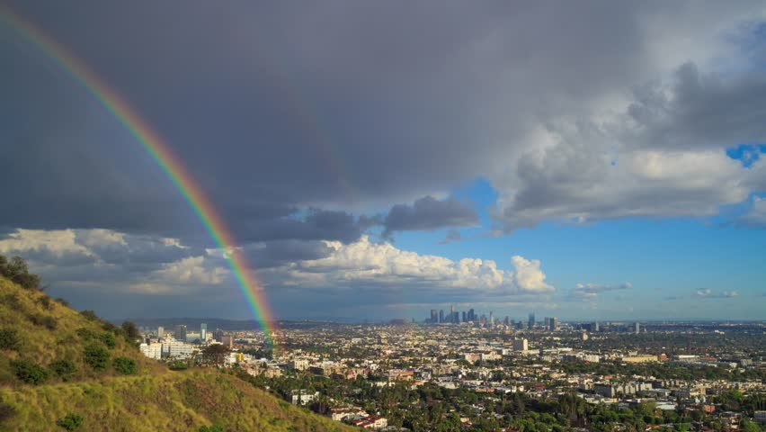 Rain passing over city of Los Angeles, changing to sunny skyline with a beautiful double rainbow. 4K UHD timelapse.