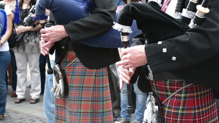 A front view of traditional scottish band musicians singing with bagpipes and drums.