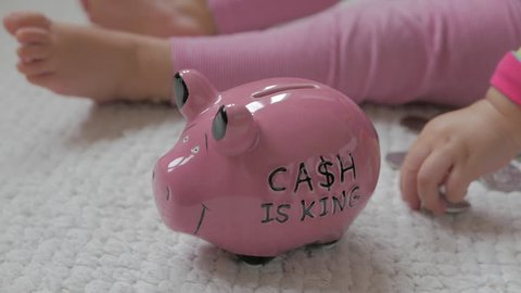 """Young girl saving money in pink piggy bank. The text """"Cash is King"""" is written on the piggy bank. CLOSE. (1 of 2)"""