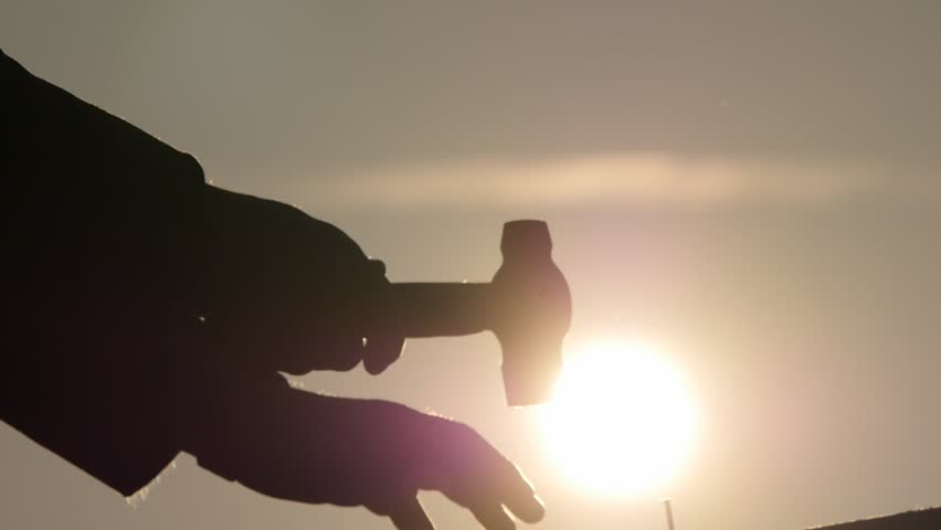 mans hands silhouette hammer a nail slow motion with bright gleaming sun