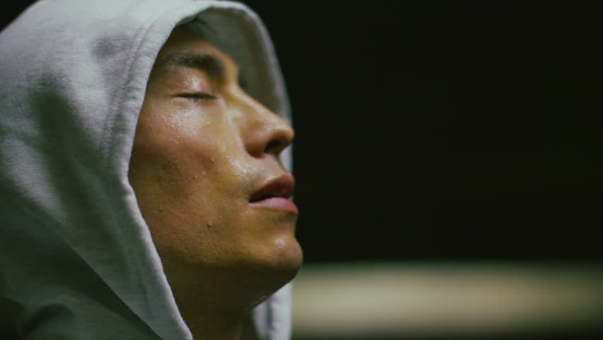 4K Hooded athlete breathing heavily and tilting his head to the light as he regains his breath in slow motion, shot on RED EPIC