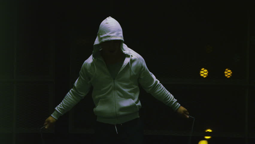 4K Slow motion hooded male athlete skipping at night with a jump rope in urban setting, shot on RED EPIC