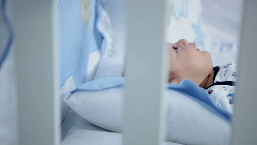 Baby in diaper lying in his crib at home in bedroom | Shutterstock HD Video #9100592