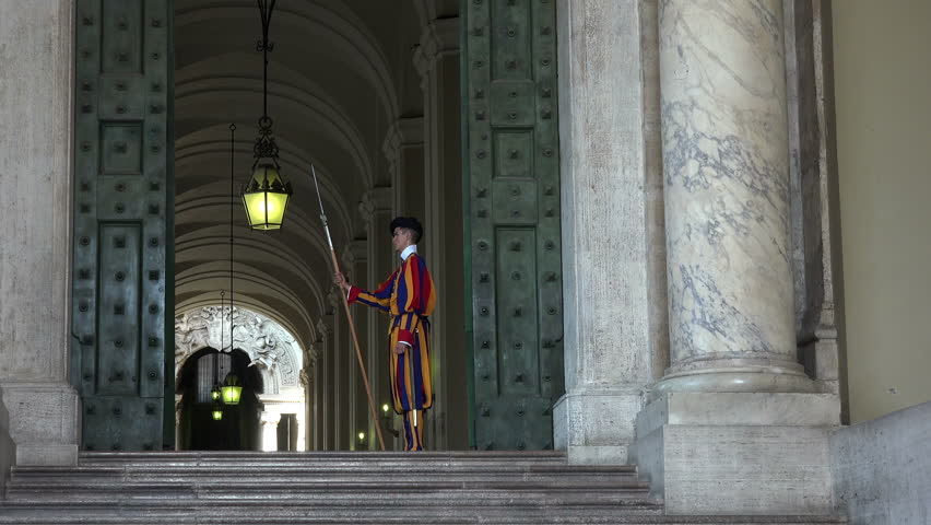 VATICAN, ITALY - SEPT 2014: Rome Italy Vatican Swiss Guard at St Peters Cathedral door. Holy See stationed at the Vatican in Rome. Papal Swiss Guard was founded in 1506. Modern military unit.