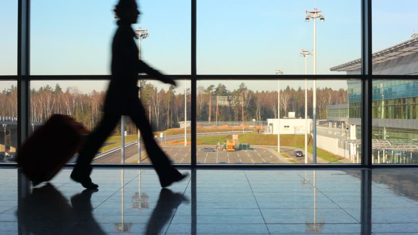 silhouettes of family hurry to aircraft against window at airport