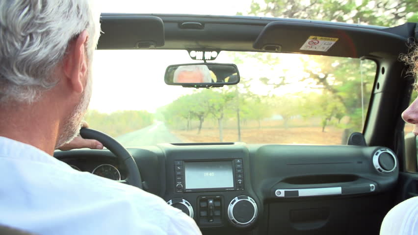 Slow motion sequence of mature couple driving open-top car along country road.Shot on Sony FS700 at frame rate of 100fps #9154202