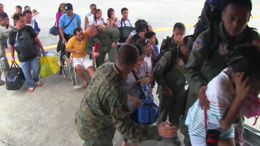 CIRCA 2010s - Injured Philippine refugees are led onto a U.S. cargo plane during Typhoon Haiyan.