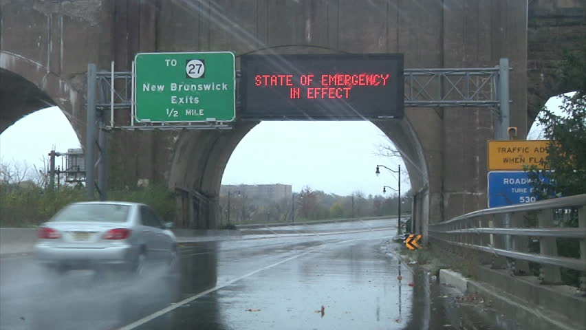 CIRCA 2010s - Waves whip the shore and roads show emergency signs during Hurricane Sandy.