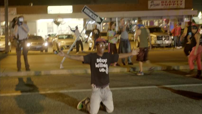 FERGUSON, MISSOURI - CIRCA 2014 - Protestors fall to their knees to oncoming police in the Ferguson riots.