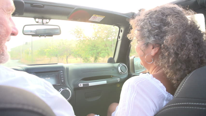 Slow motion sequence of mature couple driving open-top car along country road.Shot on Sony FS700 at frame rate of 100fps #9172763