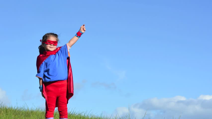 Superhero child (girl) runs in a green field against dramatic blue sky background with copy space. concept photo of Super hero, girl power, play pretend, childhood, imagination.   Shutterstock HD Video #9175202