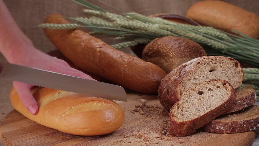 Cutting white bread of  bread knife on a wooden board | Shutterstock HD Video #9186302