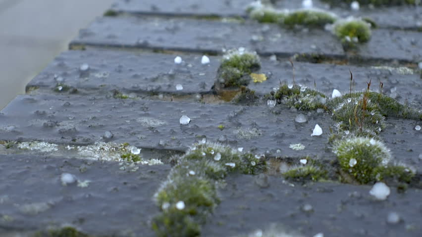 Extreme Weather - hail stones falling onto brick wall. Close up. slow motion.