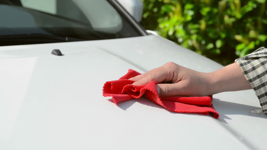 Car Care - woman polishing a white car with a red polishing cloth