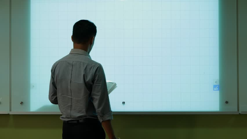 A male teacher drawing a graph using Interactive Projector Board, 21st century learning style.