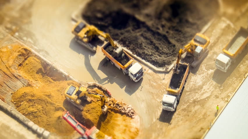 HONG KONG - JAN 23, 2015: Excavators and tipper tracks working at construction. Hong Kong. Time lapse form aerial view point, tilt shift