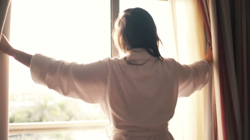Woman in bathrobe unveil curtains in room in the morning