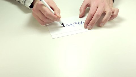 Hands writing the short note Welcome on white notepaper. The business meeting held in silence