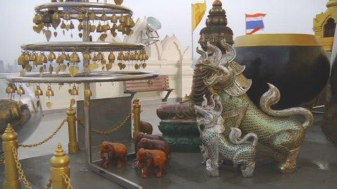 BANGKOK - CIRCA 2013: Tilt Wide Shot of statues and bells at the Golden Mount in Bangkok, Thailand