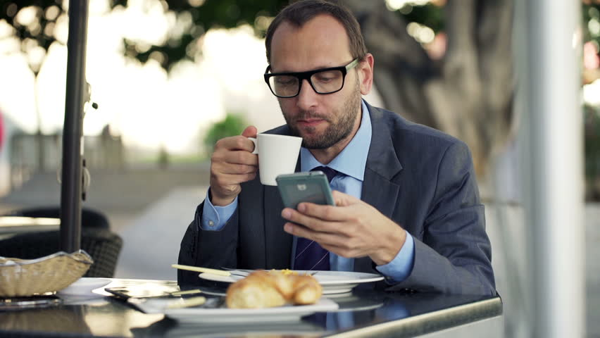 Young businessman using smartphone, drinking coffee in cafe in city    Shutterstock HD Video #9316205