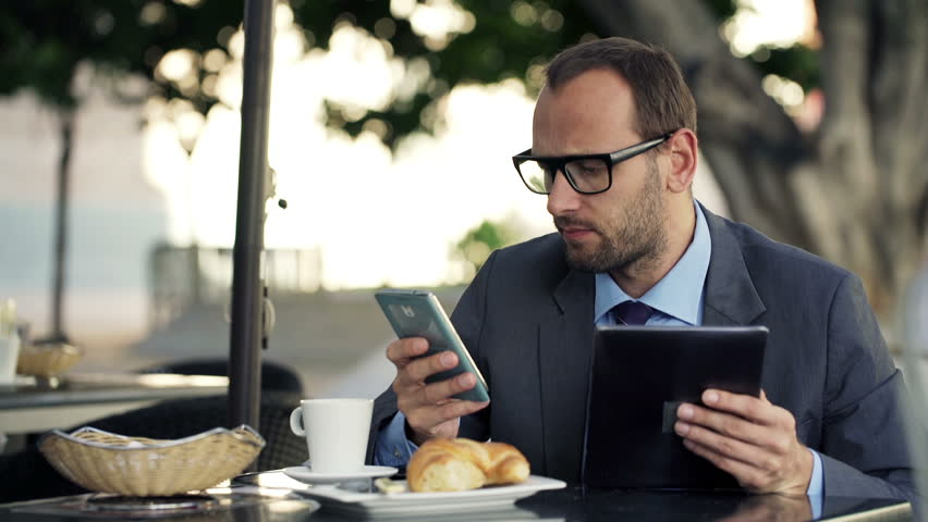 Young businessman comparing data on tablet computer and smartphone in cafe    Shutterstock HD Video #9316211