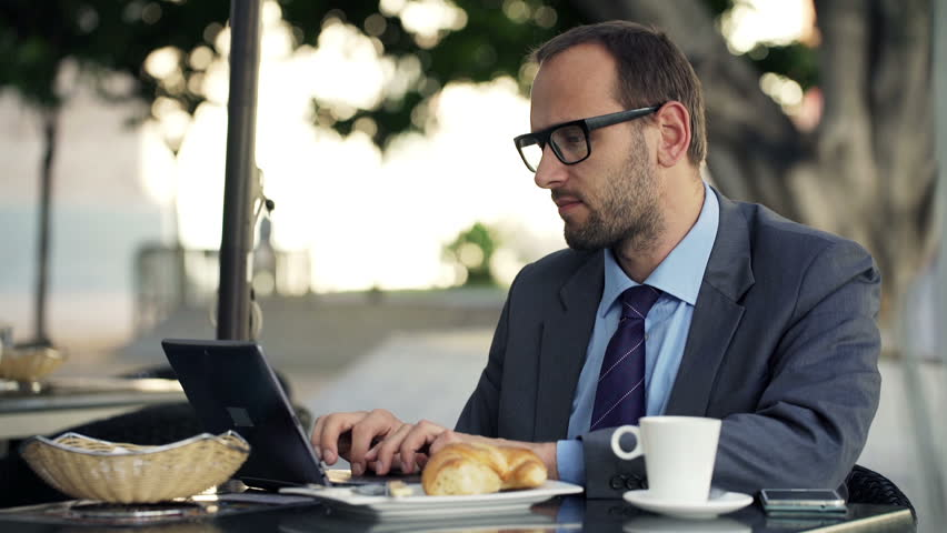 Handsome businessman working on laptop sitting in cafe in city    Shutterstock HD Video #9316229