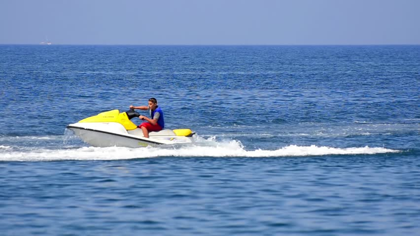 Ksamil, Albania - circa AUG. Summer resort activity on Ionian sea, A man cruises the ocean on a jet ski with sail boat on horizon on circa August, 2014 in Ksamil, Albania