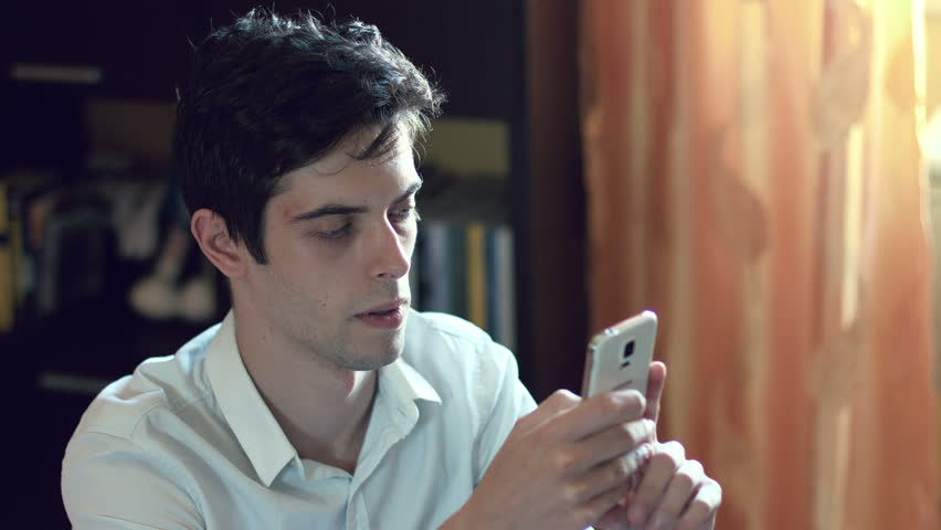 Young man composing messages with his mobile phone at home: window lateral light | Shutterstock HD Video #9339584