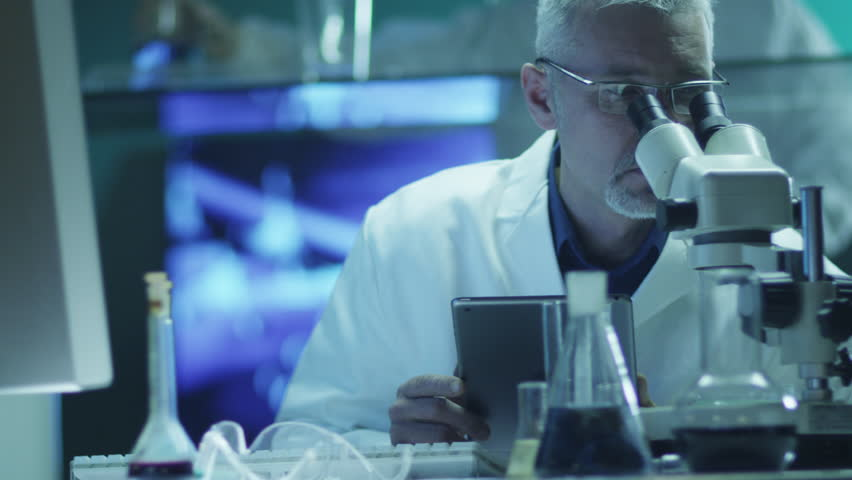 Scientist is Looking through Microscope and Using Tablet in Laboratory. Shot on RED Cinema Camera in 4K (UHD). | Shutterstock HD Video #9344519