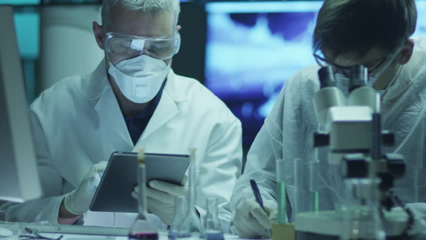 Team of Scientists is Doing Biological Researches and Writing Data into Tablet. Shot on RED Cinema Camera in 4K (UHD).