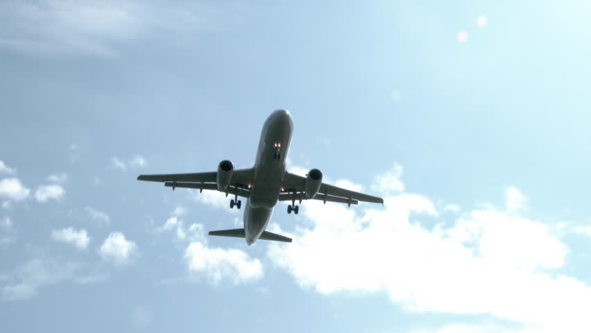 4K Commercial airline plane flying by overhead on sunny, blue sky day.